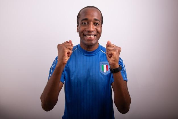 Il tifoso italiano è felice per la vittoria del tifoso italiano che celebra il ragazzo afro italiano con la maglia
