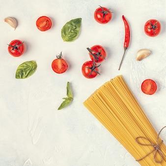 Sfondo di cibo italiano con pasta, spezie e verdure.