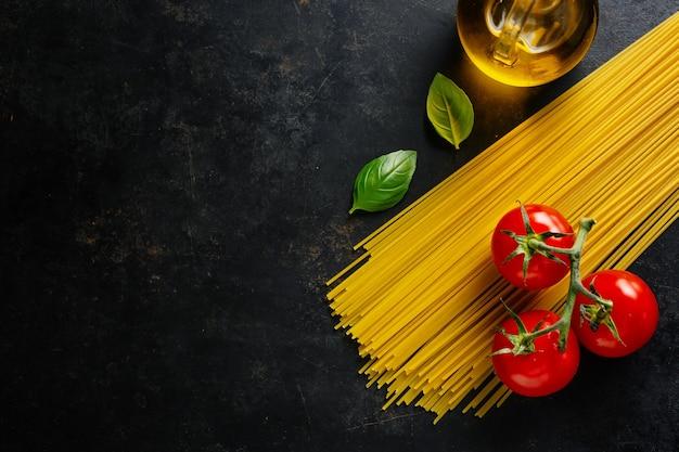 Sfondo di cibo italiano con spaghetti, pomodori, olio d'oliva su sfondo scuro.
