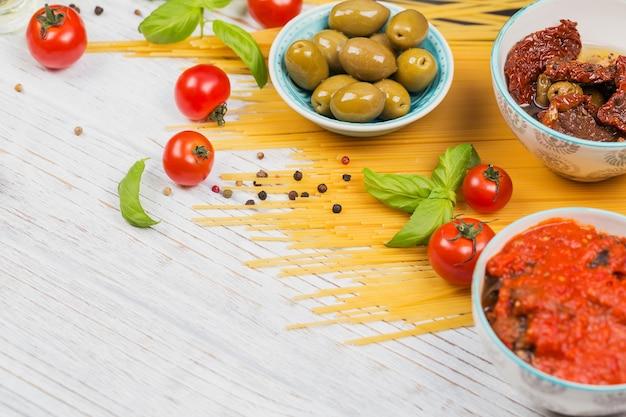 Concetto di cucina italiana. ingredienti per la preparazione degli spaghetti di pasta - pomodoro, olio d'oliva, spezie, erbe aromatiche, olive verdi, salsa di pomodoro, fondo di legno bianco. copia spazio per il testo
