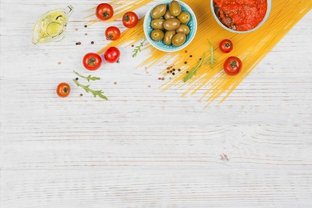 Concetto di cucina italiana. ingredienti per la preparazione degli spaghetti di pasta - pomodoro, olio d'oliva, spezie, erbe aromatiche, olive verdi, salsa di pomodoro, fondo di legno bianco. vista dall'alto con copia spazio per il testo