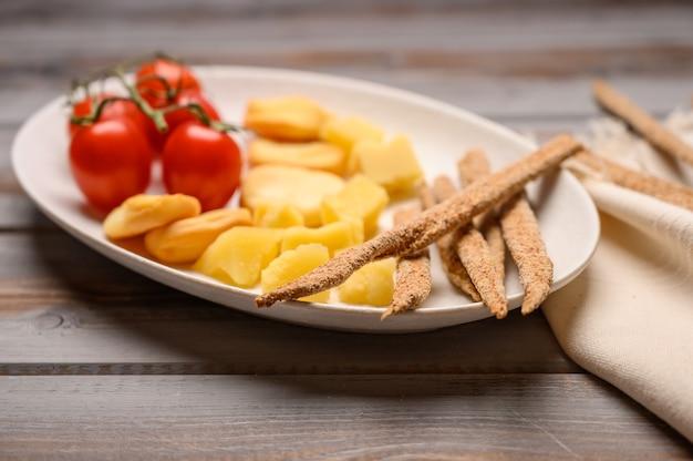 Il cibo italiano è pane grissini con prosciutto, formaggio e pomodori alle erbe su un piatto su un fondo di legno.