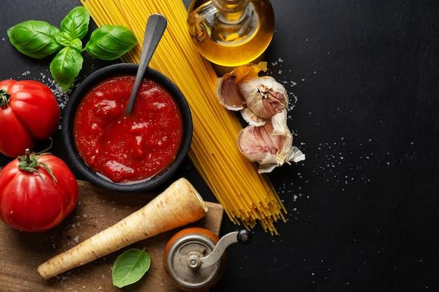 Superficie del cibo italiano con verdure spaghetti e salsa di pomodoro su sfondo scuro