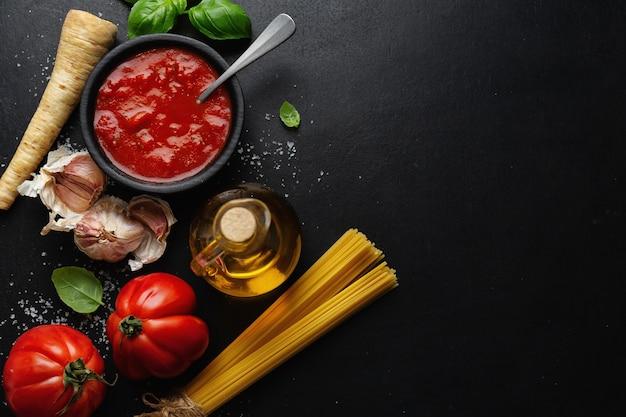 Superficie del cibo italiano con verdure spaghetti e salsa di pomodoro sulla superficie scura