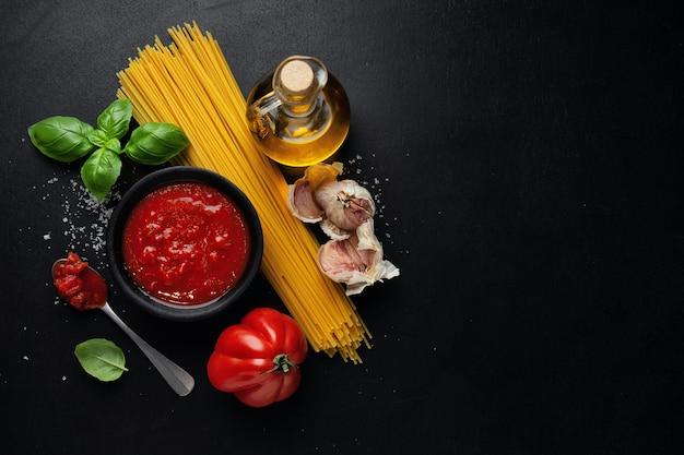 Cibo italiano con verdure spaghetti e salsa di pomodoro sulla superficie scura