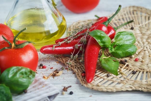 Cibo italiano con pomodori, basilico, olio d'oliva, pepe in grani, peperoncino e timo. concetto di cibo.