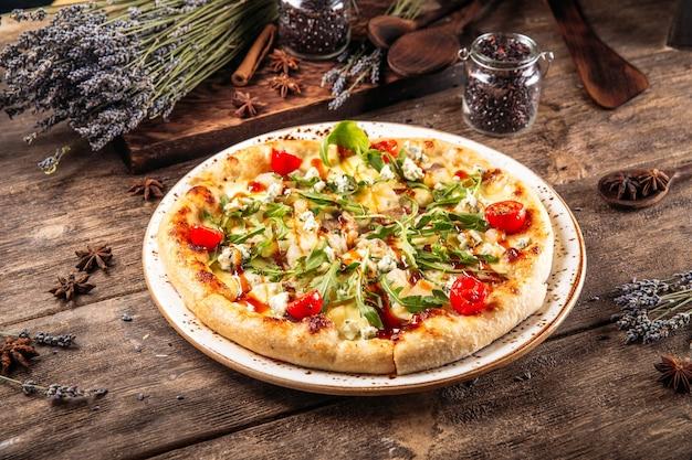 Pizza soffice pasta fresca al forno italiana con rucola e pomodori sul tavolo di legno