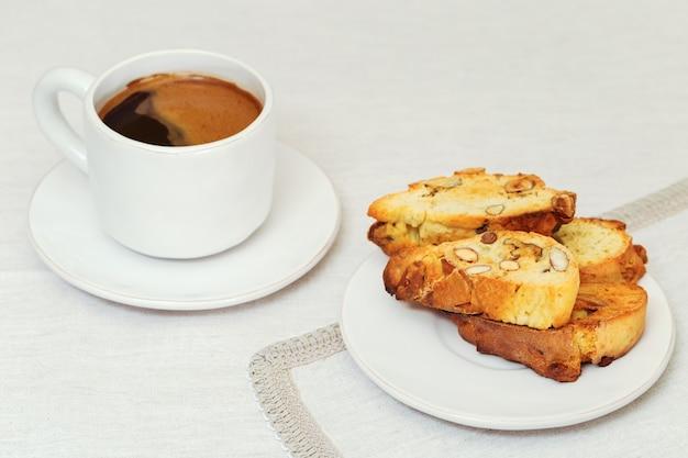 Biscotti italiani fatti in casa con noci su piatto bianco su tovaglia di tessuto cantucci e caffè