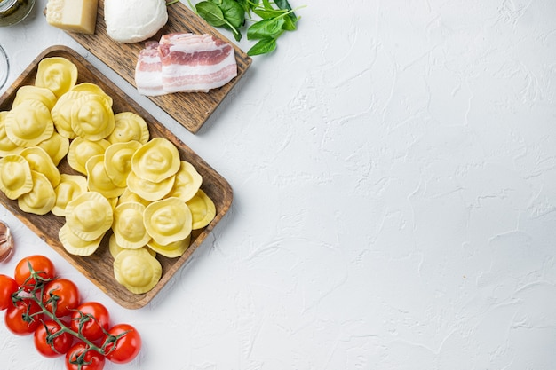 Ravioli italiani fatti in casa con ingredienti, prosciutto, basilico, pesto, set di mozzarella, sul vassoio in legno, vista dall'alto