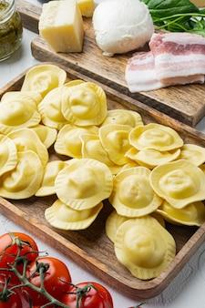 Ravioli italiani fatti in casa con ingredienti, prosciutto, basilico, pesto, mozzarella set, sul vassoio in legno, sul tavolo bianco