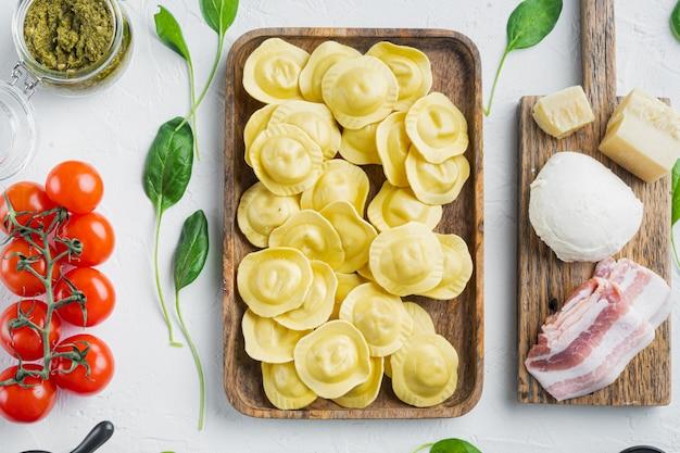 Ravioli fatti in casa italiani con ingredienti, prosciutto, basilico, pesto, mozzarella, su vassoio di legno, su bianco