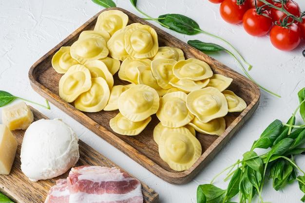 Ravioli fatti in casa italiani con ingredienti, prosciutto, basilico, pesto, set di mozzarella, sul vassoio in legno