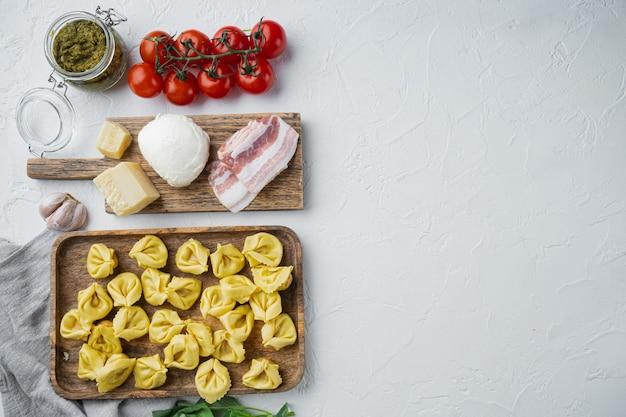 Tortellini fatti in casa italiani con ingredienti, prosciutto, basilico, pesto, set di mozzarella, sul vassoio in legno, vista dall'alto laici piatta