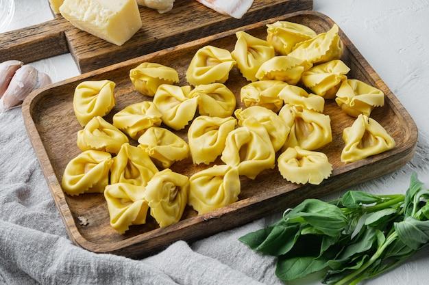 Tortellini fatti in casa italiani con ingredienti, prosciutto, basilico, pesto, set di mozzarella, sul vassoio in legno