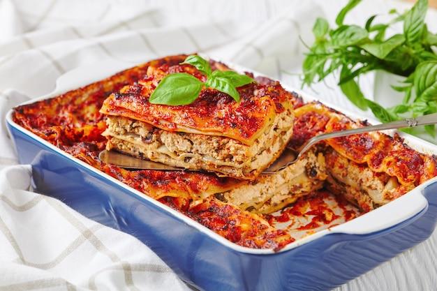 Casseruola di lasagne italiane con tofu sodo, funghi, salsa di pomodoro al forno, servita su una teglia con basilico fresco su una superficie di legno bianco, primo piano