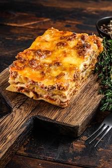 Lasagne all'italiana con ragù alla bolognese e carne di manzo tritata. fondo di legno scuro. vista dall'alto.