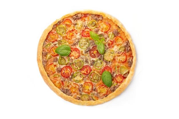 Pizza italiana di carne con pomodori, tre tipi di carne (salsicce, pancetta, carne macinata), mozzarella decorata con foglie di basilico verde.