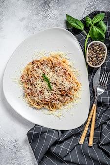 Pasta italiana alla bolognese. spaghetti con carne e salsa al pomodoro in un piatto. sfondo grigio. vista dall'alto