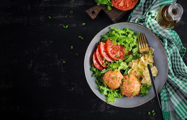 Pasta italiana. farfalle con polpette e insalata sul tavolo scuro. cena. vista dall'alto, in alto.