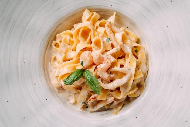 Fettuccine di pasta italiana in salsa cremosa con gamberetti su un piatto