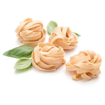 Fettuccine di pasta italiana nido e foglie di basilico isolati su sfondo bianco ritaglio