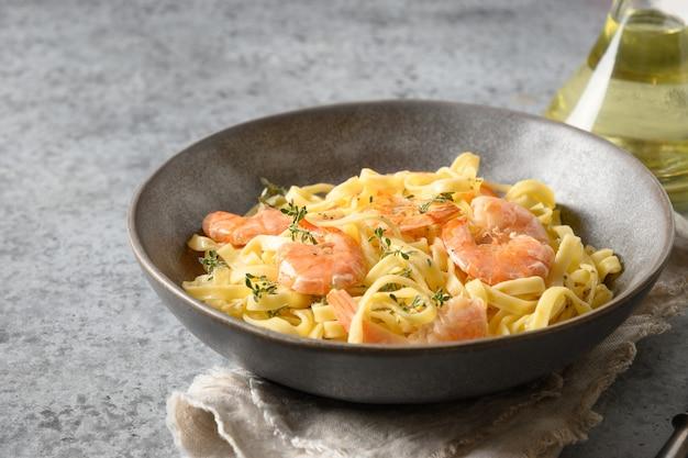 Fettuccine di pasta italiana con gamberetti nella ciotola sul tavolo grigio. avvicinamento.