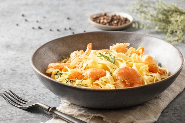 Fettuccine di pasta italiana con gamberetti decorato rametto di rosmarino nella ciotola sul tavolo grigio. avvicinamento.