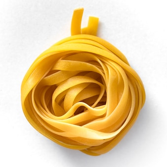 Pasta italiana, tagliatelle o pasta su un tavolo di marmo bianco.