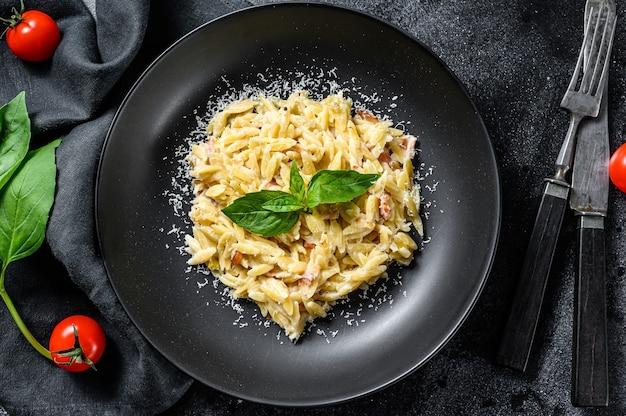 Pasta italiana orzo. ricetta con salsa di panna, pancetta e basilico. risoni preparati. fondo in legno nero. vista dall'alto.
