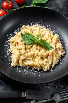Pasta italiana orzo. ricetta con salsa di panna, pancetta e basilico. risoni preparati. sfondo nero in legno. vista dall'alto