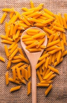 Penne di pasta italiana, carboidrati su fondo rustico