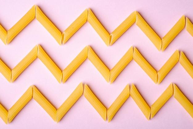 Pasta italiana, crudo tubo di penne maccheroni a zig-zag su sfondo rosa, vista dall'alto, cibo astratto