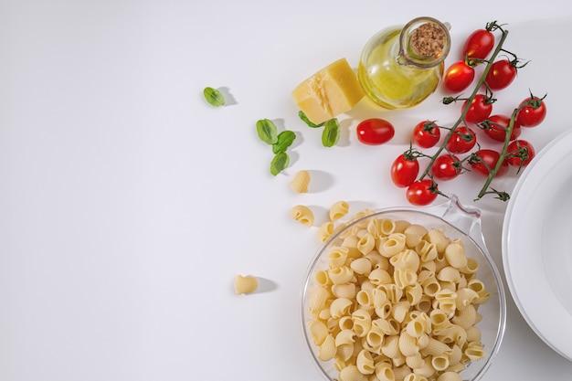 Pasta italiana rigate mature pomodorini freschi, basilico, parmigiano e olio d'oliva sul tavolo. vista dall'alto. spazio per il testo
