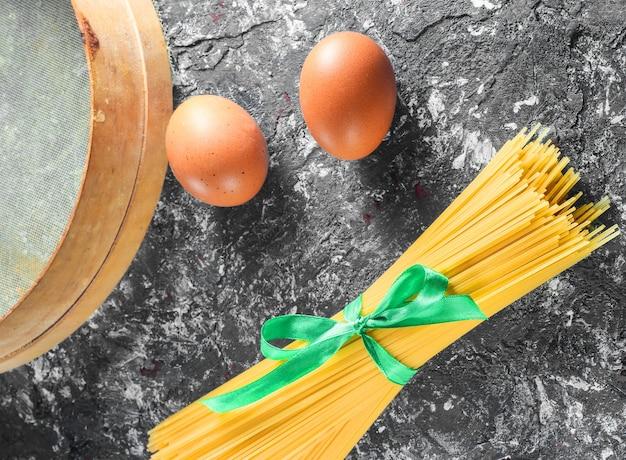 Pasta italiana, setaccio, uova su sfondo grigio cemento
