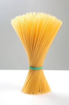 Spaghetti di pasta italiana su sfondo bianco e grigio. prodotti di farina e cibo in cucina