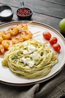 Spaghetti di pasta italiana con gamberi alla griglia, set di salsa al pesto, su piatto, su vecchio fondo di legno scuro