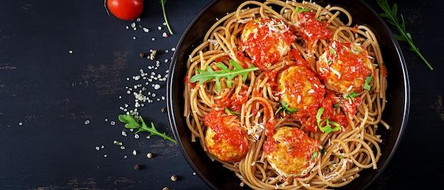 Pasta italiana. spaghetti con polpette e parmigiano in banda nera su fondo di legno rustico scuro. cena. vista dall'alto. concetto di cibo lento