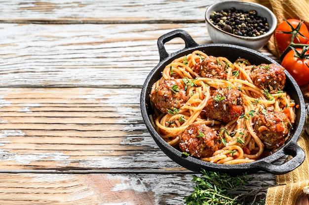 Spaghetti di pasta italiana con salsa di pomodoro e polpette in padella di ghisa con parmigiano