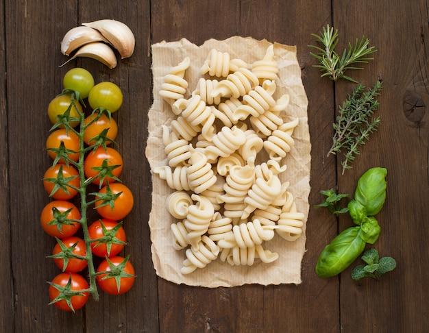 Pasta italiana, pomodori ed erbe su una superficie di legno