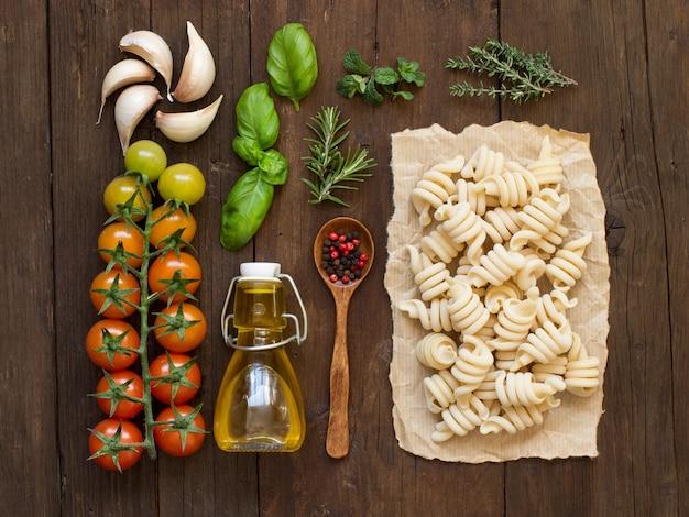 Pasta italiana, verdure, erbe aromatiche e olio d'oliva su una superficie di legno