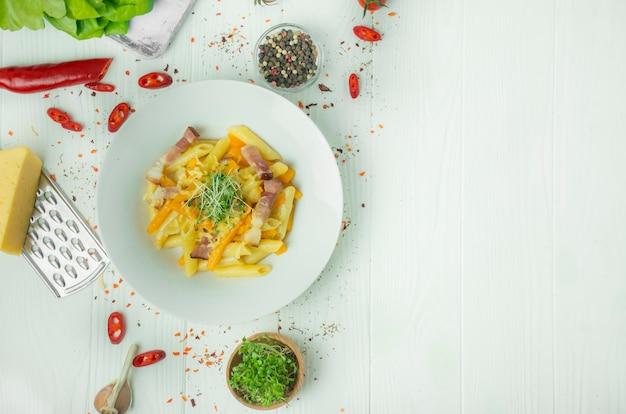 Pasta italiana con formaggio, zucca e pancetta fritta, servita su un piatto bianco. sfondo in legno chiaro spazio per il testo.
