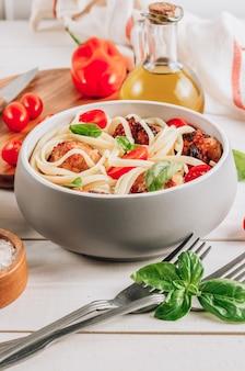 Pasta italiana con polpette di pollo, pomodori e basilico