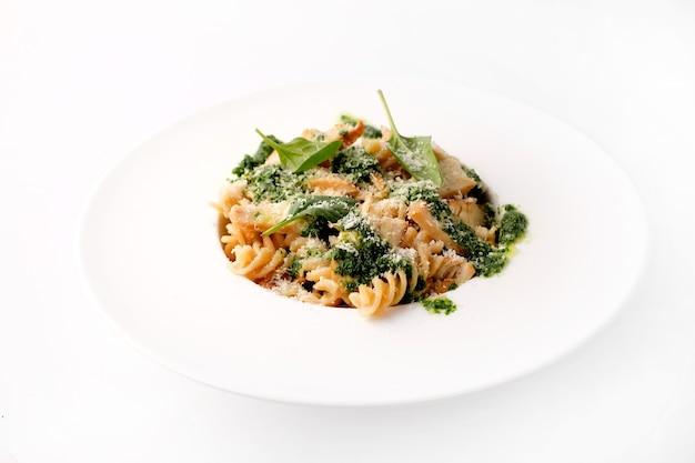 Pasta italiana con fette di pollo di carne pesto di formaggio e foglie verdi su un ampio piatto bianco vista dall'alto su sfondo bianco