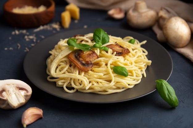Pasta italiana con funghi e formaggio su uno spazio buio