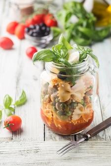 Pasta italiana con salsa di pomodoro, funghi, piselli e formaggio in un barattolo. cibo per lavoro e ufficio