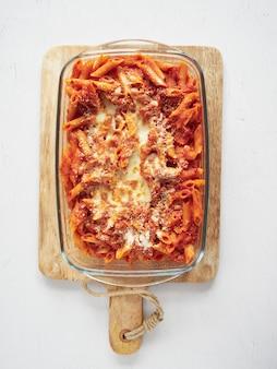 Pasta italiana del pene con salsa di pomodoro e parmigiano gratinato su una teglia di vetro e un tagliere di legno.