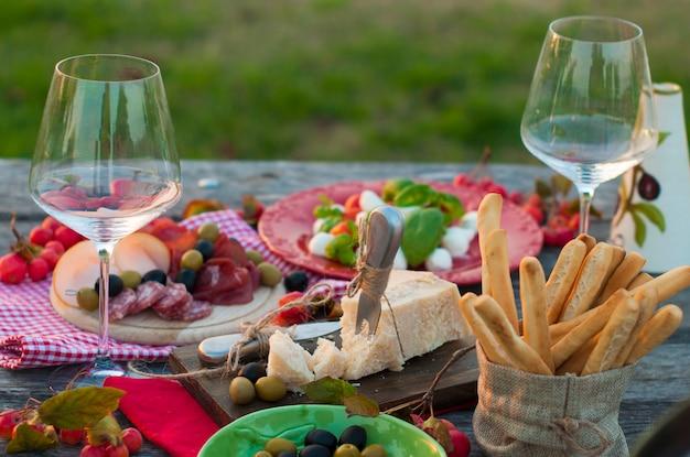 Picnic italiano con vino rosso, parmigiano, prosciutto, insalata caprese e olive. pranzo all'aperto e tavola di legno ed erba verde. spuntini tradizionali.