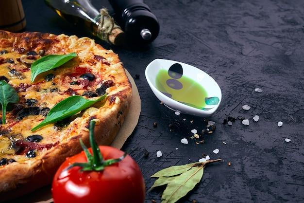 Pizza italiana e ingredienti su sfondo scuro. pomodori, olio d'oliva, erbe aromatiche, sale e spezie.