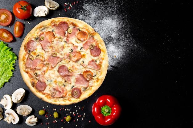 Pizza e ingredienti italiani. funghi, pomodori, pepe, sale, erbe aromatiche e vivo su un tavolo di cemento nero. vista dall'alto