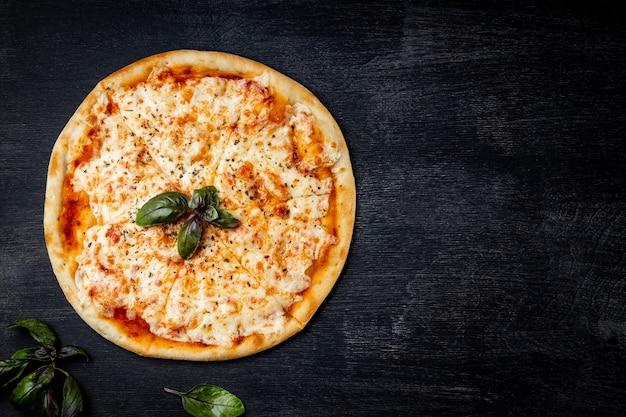 Pizza italiana margarita su sfondo nero, vista dall'alto, spazio libero per il testo.